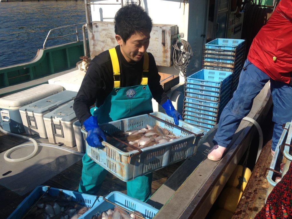漁港で魚の荷揚げをする漁業者